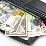 Various currencies in purse Royalty Free Stock Image