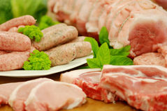 Various cuts of Pork. Various cuts of british pork on butcher's block with fresh parsley and mint Stock Photos