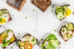 Various danish open sandwiches Smorrebrod. Set of various danish open sandwiches Smorrebrod with fish, egg and fresh vegetables, white marble background copy Stock Photography