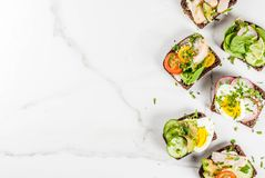 Various danish open sandwiches Smorrebrod. Set of various danish open sandwiches Smorrebrod with fish, egg and fresh vegetables, white marble background copy Royalty Free Stock Photography