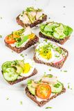 Various danish open sandwiches Smorrebrod. Set of various danish open sandwiches Smorrebrod with fish, egg and fresh vegetables, white marble background copy Stock Images