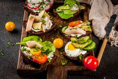 Various danish open sandwiches Smorrebrod. Set of various danish open sandwiches Smorrebrod with fish, egg and fresh vegetables, dark background copy space Stock Photo