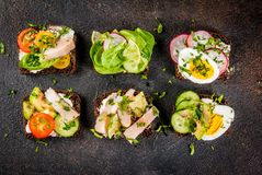 Various danish open sandwiches Smorrebrod. Set of various danish open sandwiches Smorrebrod with fish, egg and fresh vegetables, dark background copy space above Royalty Free Stock Photos