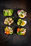 Various danish open sandwiches Smorrebrod. Set of various danish open sandwiches Smorrebrod with fish, egg and fresh vegetables, dark background copy space above Stock Photo