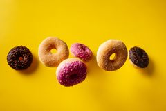 Free Various Decorated Doughnuts In Motion Falling On Yelloy Background Royalty Free Stock Photos - 161499378