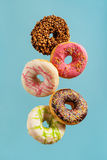 Various decorated doughnuts in motion falling on blue background Stock Photos