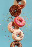 Various decorated doughnuts in motion falling on blue background Royalty Free Stock Photography