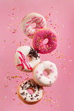 Various decorated doughnuts in motion falling on pink background Stock Images