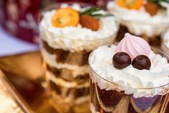 Variety of panacota italian desserts in glass. Various desserts made of pastry cream, almond, cherry and kumquat in glass stock images