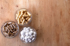 Various dietary supplements. Bowls of various dietary supplements on wooden background. From top view Royalty Free Stock Images