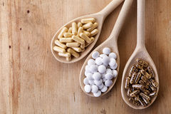 Various dietary supplements. Wooden spoons of various dietary supplements on wooden background stock images