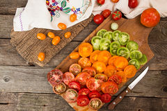 Various different color organic homegrown tomatoes on board. Cut Royalty Free Stock Images