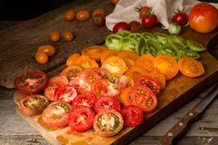 Various different color organic homegrown tomatoes on board. Cut Royalty Free Stock Photography