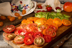 Various different color organic homegrown tomatoes on board. Cut Stock Photography