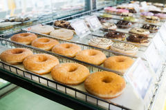 Various donuts on shelf. Donuts on shelf in bakery shop stock images