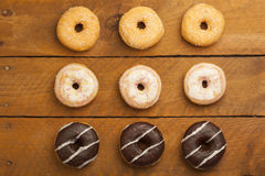 Various donuts on wood Stock Images