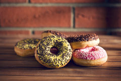 Various donuts on wooden table stock image