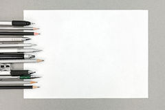 Various drawing tools and blank sheet of paper on gray office de Royalty Free Stock Photography