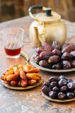 Various of dried dates or kurma in a vintage plates and tea. On a rusty background Royalty Free Stock Images
