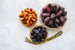 Various of dried dates or kurma in a vintage plates. Top view. White stone background Royalty Free Stock Photo