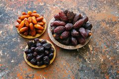 Various of dried dates or kurma in a vintage plates. Various of dried dates or kurma in a vintage plates on a rusty background Stock Photos
