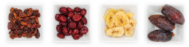 Various dried fruits in white bowls royalty free stock images