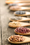 Various dried legumes in wooden spoons Stock Photos