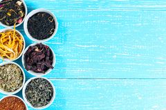 Various dried medicinal herbs and teas in several bowls on blue wooden background. From above. Copyspace Royalty Free Stock Photo