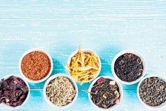 Various dried medicinal herbs and teas in several bowls on blue wooden background from above. Copyspace Stock Image
