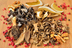 Various dried mushrooms. Penny Bun or Cep, Morels, Horn of Plenty mushrooms, Golden Bootleg mushrooms and Trumpet Chanterelle mushrooms, left on wooden Stock Photo