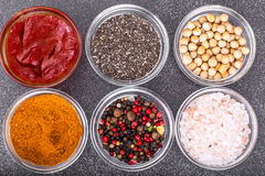 Various dry spices, sauces and cereals in glass molds on backgro Stock Images