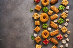 Various Eastern sweets on a rustic brown background. Baklava, delight, cookies. Top view, copy space royalty free stock photography