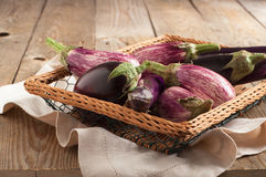 Various Eggplants on wooden table Stock Photos