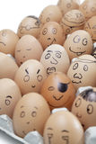 Various facial expressions painted on brown eggs arranged in carton Stock Image
