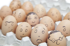 Various facial expressions painted on brown eggs in egg carton Stock Image