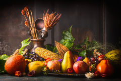 Various fall fruits and vegetables on dark rustic kitchen table at wooden background, side view Royalty Free Stock Image