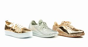 Various fancy sneakers in shiny metallic colors. Several types of fashionable sneakers in shiny metallic colors,  on white backgroud Stock Images