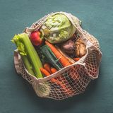 Various farm organic vegetables from local market in net string reusable bag on rustic background, top view . Clean and healthy royalty free stock photography