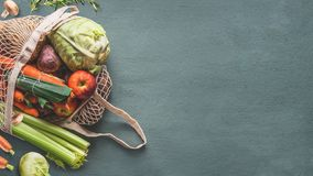 Various farm organic vegetables from local market in net string reusable bag on rustic background, top view with copy space for. Your design, banner. Clean and stock photo