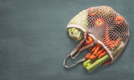 Various farm organic vegetables from local market in net string shopping bag on rustic background, top view with copy space for. Your design, banner. Clean and royalty free stock photos
