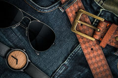 Various fashions of sunglasses, wrist watches and belt. In jeans Royalty Free Stock Photos