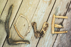 Various figures and letters from driftwood and colored stones on a simple wooden gray background. Top view. Stock Image