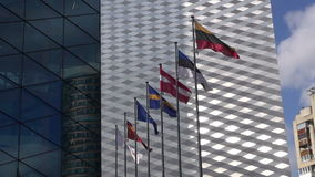 Various flags in wind. On modern wall background stock footage