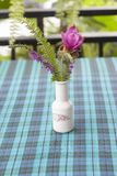 Various flowers in the vase are located on the tablecloth. stock photography