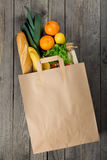 Various food in paper bag on wooden background Royalty Free Stock Images