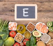 Vitamine E food sources, top view on wooden background. Various food sources of vitamine E, top view on wooden background Royalty Free Stock Photos