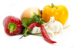 Various foods on white. Foodstuffs including bell peppers, onion, garlic, chillies and coriander herbs isolated on a white background Stock Photography