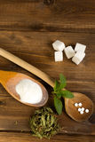 Various forms of stevia sweetener. Various forms of stevia natural sweetener plus real sugar lumps on a wooden table Stock Photo