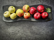 Various fresh apples on black plate Stock Photo