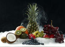 Various fresh fruits from coconut, pineapple, ripe, apples and grape on the white table in black background in smoke vapor stock photos